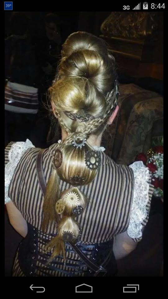 Photo of the detail on a steampunk themed hairdo, with gears and other baubles.