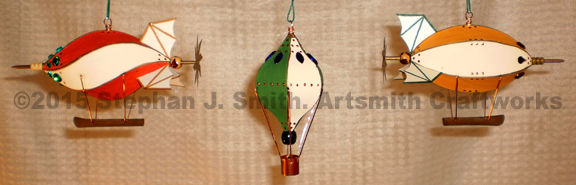 Photo of a set of three steamunk airship Christmas ornaments. Colors, red, gold and green.